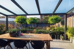 Moderne Gumax® Terrasoverkapping in mat antraciet van 5,06 x 3,5 meter met glazen dakplaten inclusief Gumax zonwering en glazen spie