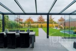 Moderne Gumax® Terrasoverkapping in mat antraciet van 8,06 x 4,0 meter met glazen dakplaten inclusief Gumax LED verlichting en glazen schuifwanden