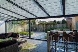 Moderne Gumax® Serre aanbouw in mat antraciet van 8,06 x 4 meter met ingekorte glazen dakplaten inclusief Gumax zonwering, LED verlichting, glazen schuifwanden en vaste polycarbonaat zijwand