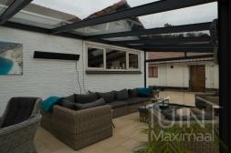 Moderne Gumax® Overkapping aan huis in mat antraciet van 7,06 x 3,5 meter met glazen dakplaten inclusief Gumax zonwering en glazen spie