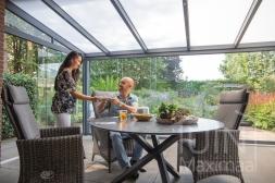 Moderne Gumax® Terrasoverkapping in mat antraciet van 6,06 x 3,5 meter met een ingekorte breedte met opaal polycarbonaat dakplaten inclusief Gumax glazen schuifwanden en glazen spie
