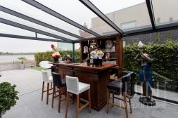 Moderne Gumax® Overkapping aan huis in mat antraciet van 8,06 x 4,0 meter met glazen dakplaten inclusief Gumax LED verlichting en glazen schuifwanden