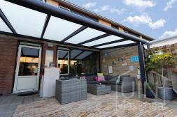 Moderne Gumax® Terrasoverkapping in mat antraciet 6,06 meter bij 3 meter met melkglas dak
