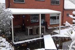 Moderne Gumax® Terrasoverkapping in mat wit aan huis, in de sneeuw