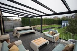 Moderne Gumax® Serre aanbouw in mat antraciet van 7,06 x 4 meter met opaal polycarbonaat dakplaten inclusief Gumax LED verlichting, glazen schuifwanden en Glazen spie
